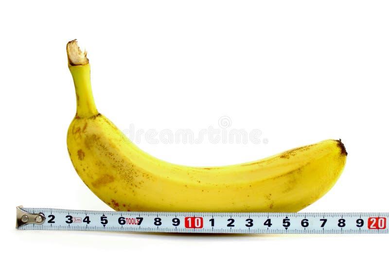 Große Banane und messendes Band auf Weiß lizenzfreie stockfotografie