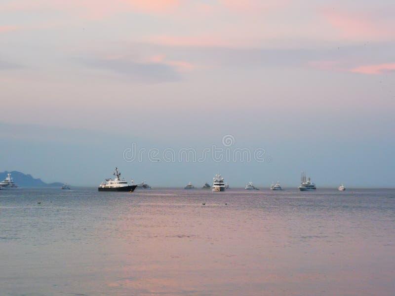 Große Boote im Ozean verankert während eines schönen rosa Sonnenuntergangs an den Feiertagen in St Tropez Frankreich stockfoto