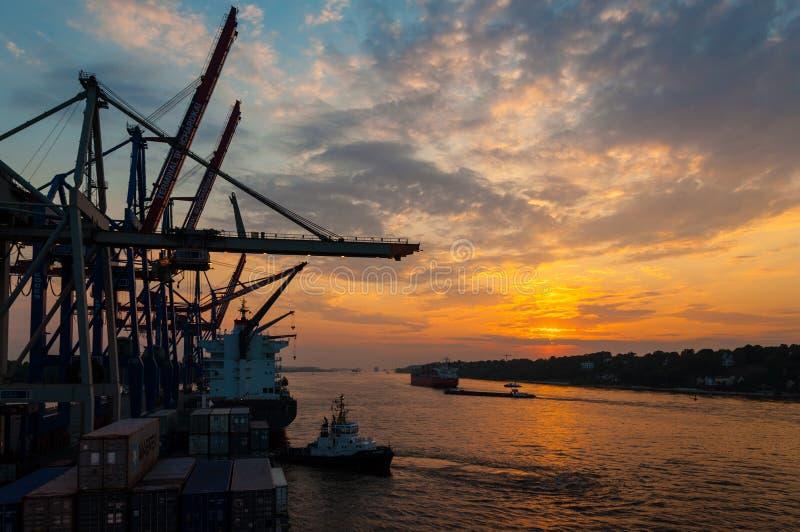 Große Containerschiffe am Containerbahnhof Buchardkai in Hamburg an der Dämmerung stockfotos