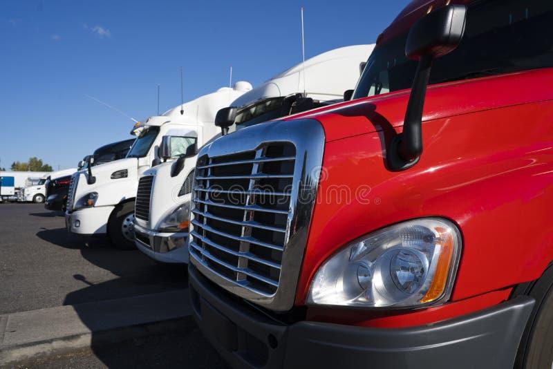 Große der Anlagen LKWs halb in der Reihe auf Fernfahrerrastplatzteil der Fahrerhausansicht stockfotografie