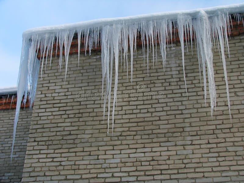 Große Eiszapfen auf dem Dach lizenzfreies stockfoto
