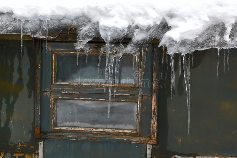Große Eiszapfen auf dem Dach nahe einem kleinen Fenster in einem alten Landhaus an einem Wintertag, Tauwetter, Vorfrühling lizenzfreies stockfoto