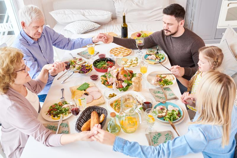 Große Familie, die Anmut am Abendessen sagt lizenzfreie stockfotos