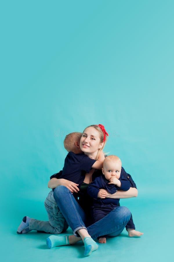 Große Familie Junge schöne blonde Frau mit Kindern, Spaßsöhne umfassen die Mutter lizenzfreie stockfotos