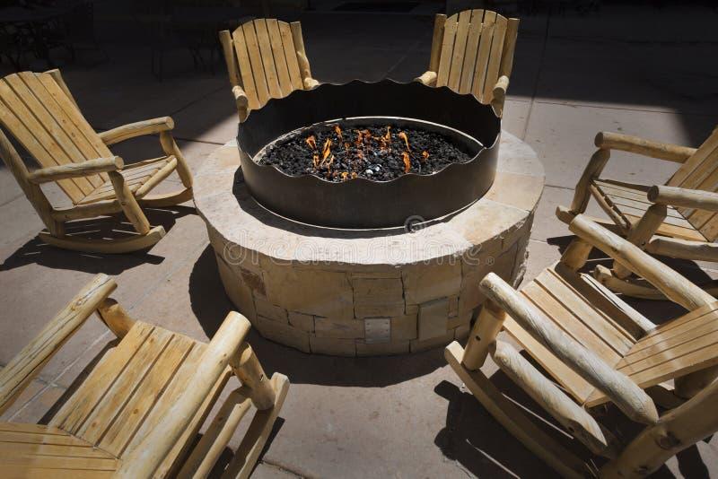 Große Feuergrube im Freien umgeben von den hölzernen Schaukelstühlen stockfotografie