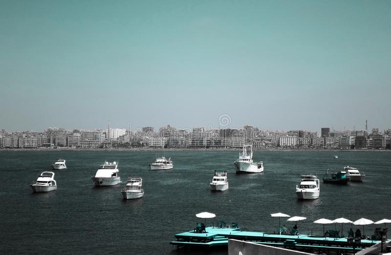 Große Fischboote, die nahe der Zitadelle von Qaitbay auf der Küste von Alexanderia, Ägypten parken stockbild