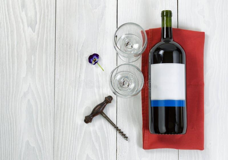 Große Flasche Rotwein auf Umhüllungsserviette mit Gläsern auf Weiß lizenzfreies stockbild