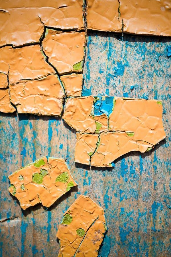 Große Fragmente der alten Schalenfarbe färben ockerhaltig, auf einer alten Holzoberfläche lizenzfreie stockfotos