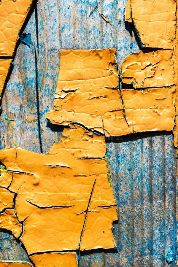 Große Fragmente der alten Schalenfarbe färben ockerhaltig, auf einer Holzoberfläche stockfoto