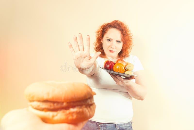 Große Frau essen Schnellimbiß Fettes Mädchen des roten Haares mit Burger Unhealth stockfoto