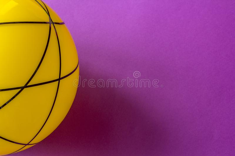 Große gelbe Glaskugel auf einem violetten Hintergrund Stillleben des gestreiften gelben Balls auf heller violetter Tabelle stockbild