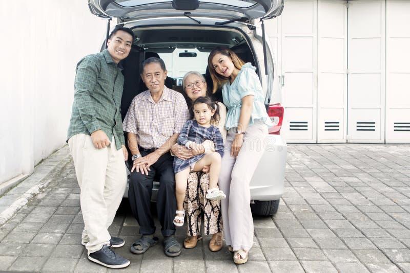 Große glückliche Familie, die auf dem Stamm ihres Autos sitzt lizenzfreie stockfotos
