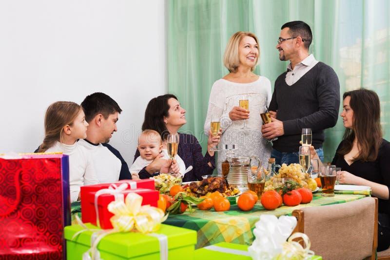 Große glückliche Familie, die am Feiertagstisch sitzt lizenzfreie stockfotos