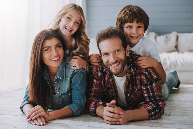 Große glückliche Familie liegt zusammen auf Boden stockfoto