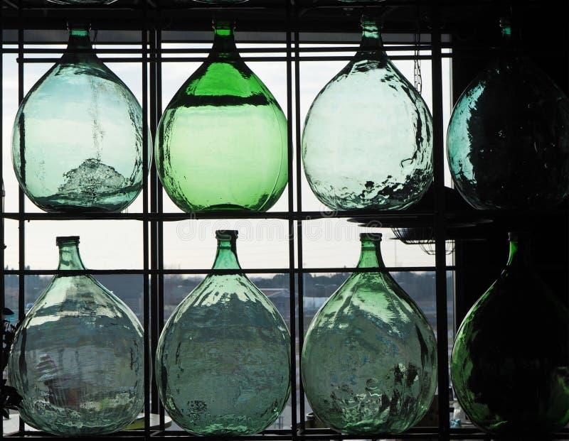 Große Glaskorbflaschen für Wein gegen das Licht eines Fensters stockbild