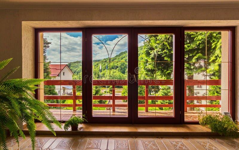 Große Glastüren im Haus, über dem ein Panorama von Bergen unter dem blauen Himmel sich öffnet stockbilder