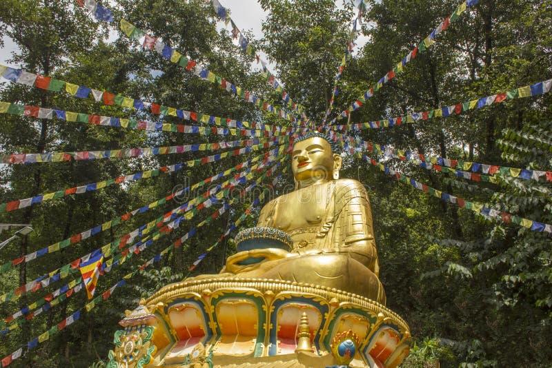 Große goldene Statue von einem Sitz-Buddha gegen den Hintergrund eines grünen Waldes mit tibetanischen Gebetsflaggen lizenzfreie stockfotografie