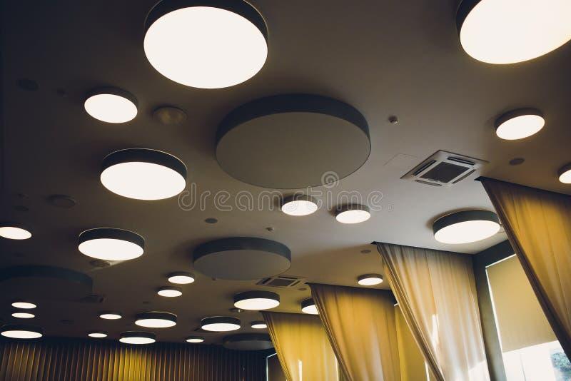 Große graue Elfenbeinhexagone mit Licht nach innen ist auf Decke mit klassischen Büroquadraten im moderner Entwurfs-Studio, groß stockfotografie