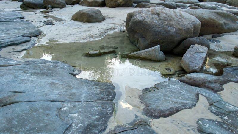 Große graue Felsen und Flusssteine im ruhigen seichten Meerwasser, breites Bild stockfoto