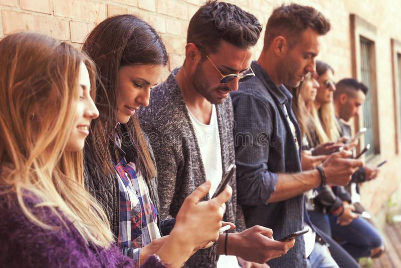 Große Gruppe Freunde, die intelligentes Telefon gegen eine rote Wand verwenden lizenzfreie stockbilder