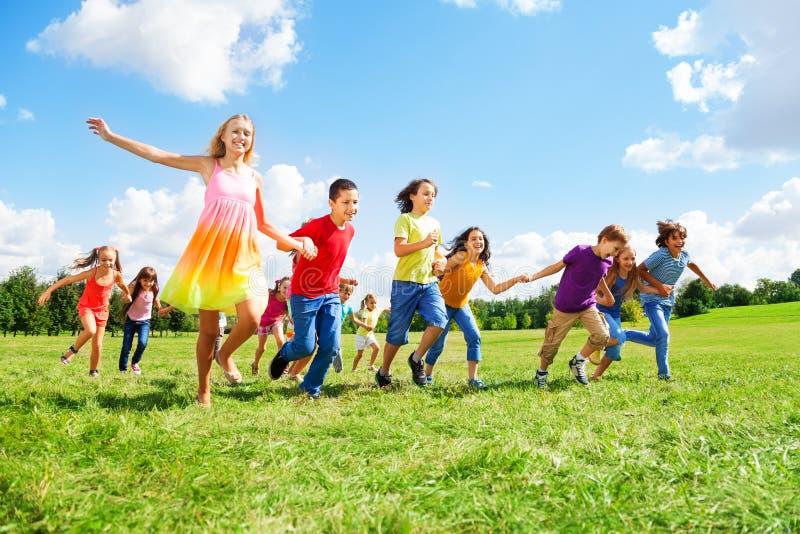 Große Gruppe Kinder, die in den Park laufen stockbilder