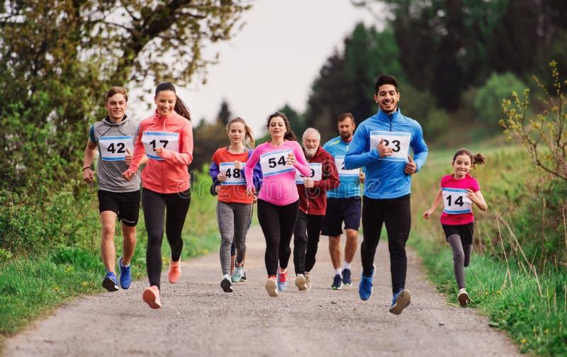 Große Gruppe multi Generationsleute, die einen Rennwettbewerb in der Natur laufen lassen stockbild