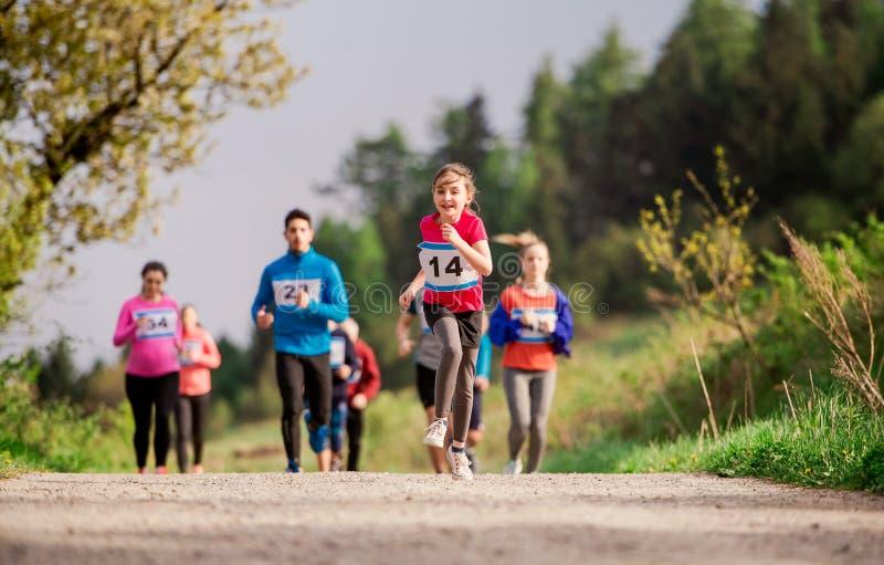 Große Gruppe multi Generationsleute, die einen Rennwettbewerb in der Natur laufen lassen lizenzfreies stockfoto