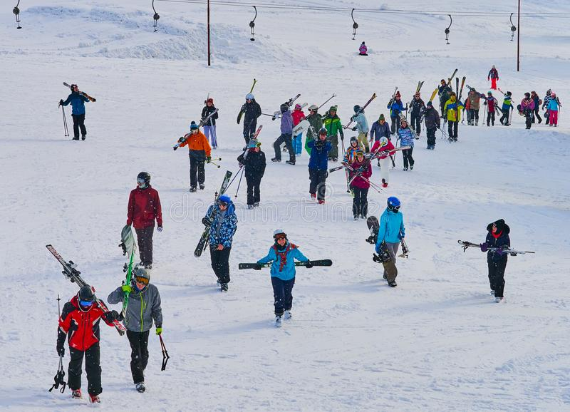 Große Gruppe Skifahrer returnig vom Ski neigt sich in einen Höhenkurort im Winter stockbild