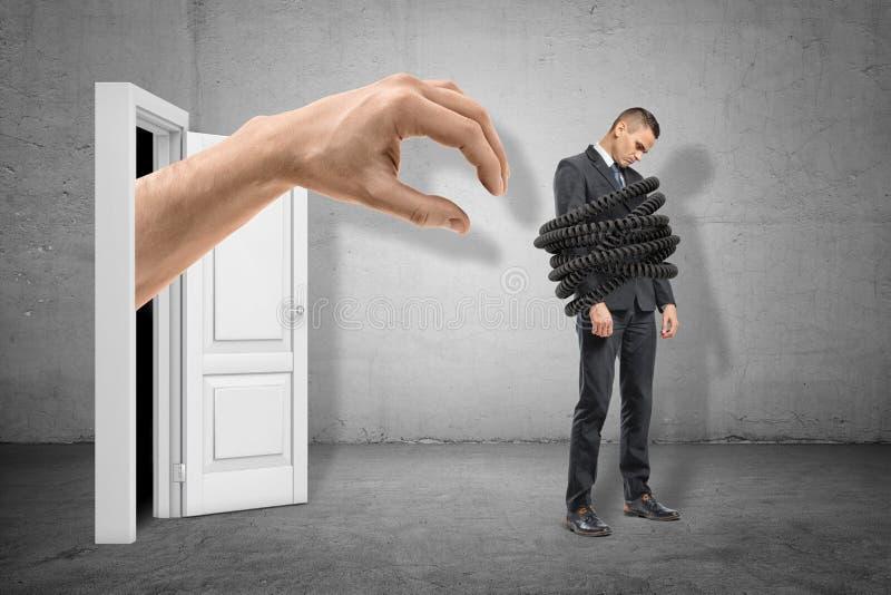 Große Hand, die zum jungen traurigen Geschäftsmann oben gebunden mit Telefonkabel auf grauem Wandhintergrund erreicht lizenzfreie stockfotos