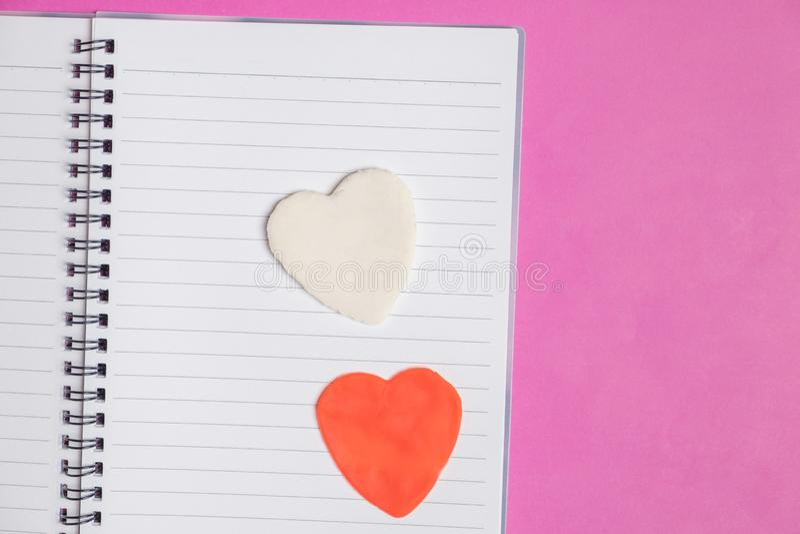 Große 2 Herzen im leeren Buch auf rosa Hintergrund mit Raum für Text, Liebesikone, Valentinstag lizenzfreie stockfotografie