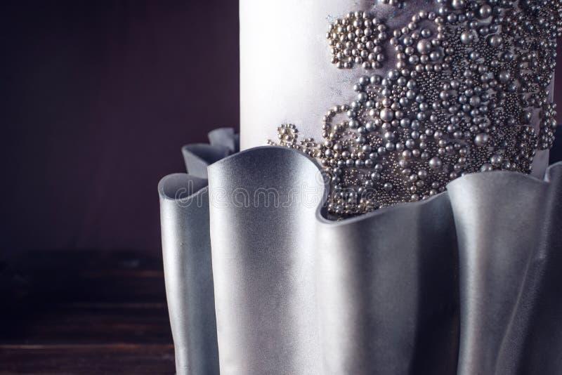 Große Hochzeitstorte verziert mit Perlen und silberner Blume lizenzfreie stockfotografie