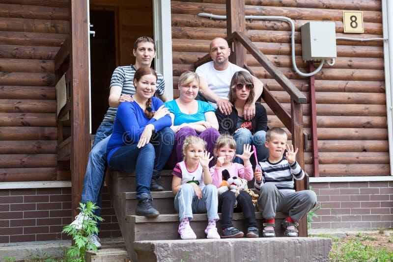 Große kaukasische Familie mit den Kindern, die auf dem Hausportal sitzen lizenzfreie stockfotografie