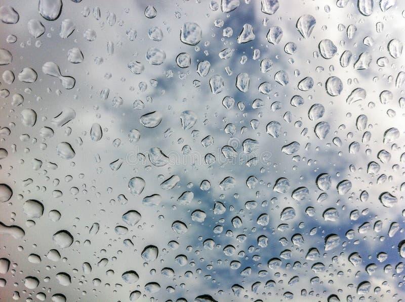 Große klare Regentropfen auf Glas gegen einen teils bewölkten Himmel lizenzfreie stockbilder