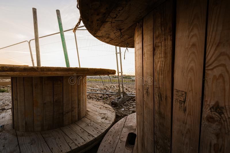 Große leere hölzerne Spule - hölzerne Spule - Holzspulen in einem Bauyard gegen einen hellen Sonnenuntergang stockbild