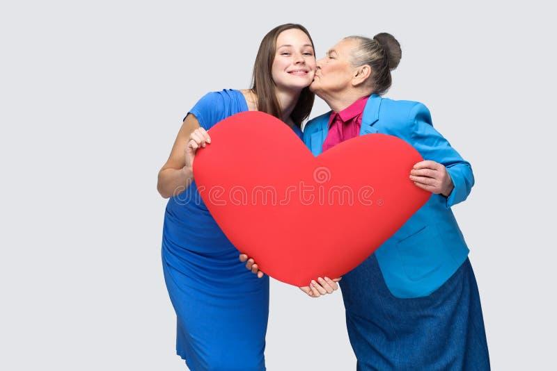Große Liebe in der Familie Junge Frau des Großmutterkusses stockbild
