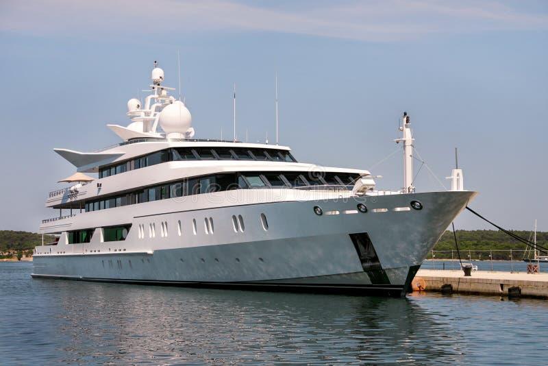 Große moderne weiße Yacht verankert im Hafen stockbilder