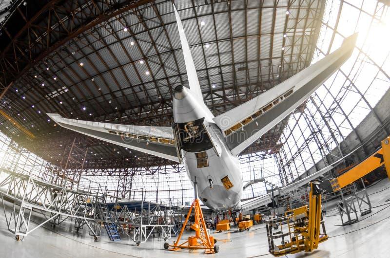 Große Passagierflugzeuge auf Service in einer hinteren Ansicht des Luftfahrthangar des Endstücks, auf der Hilfshydraulik unitand  lizenzfreies stockbild
