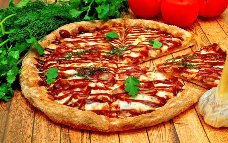 Große Pizza mit einem Grill auf einem Holztisch stockfotos