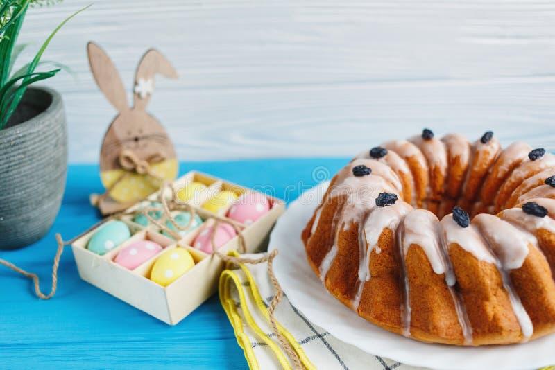 Große Platte mit Kuchen und handgemalten bunten Eiern, auf Tuch auf blauem Hintergrund Abschluss oben Dekoration für Ostern, stockbild