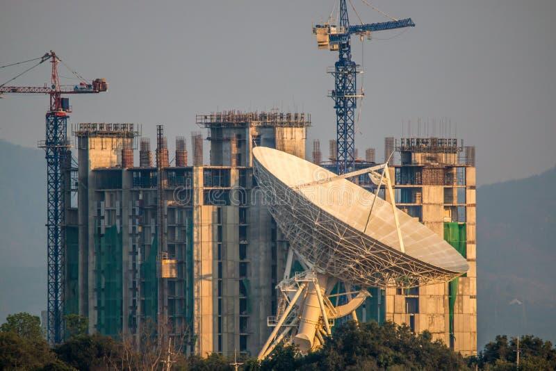 Große Satellitenschüssel auf dem Gebäude onstruction Hintergrund stockbild