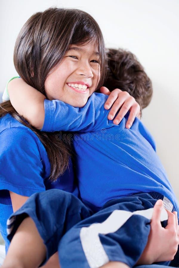 Große Schwester, die ihren behinderten kleinen Bruder hält lizenzfreies stockfoto
