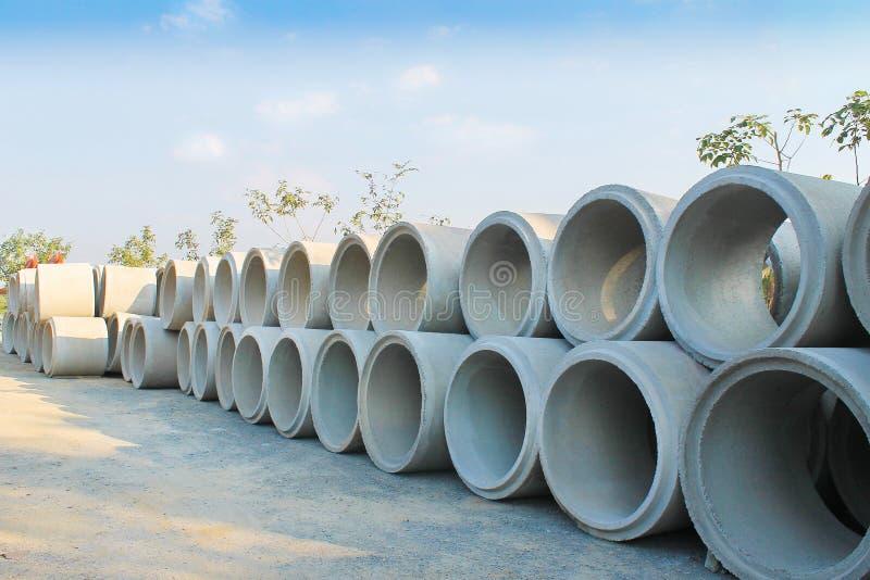 Große Stapel der konkreten Abwasserleitungen aus den Grund bereiten sich für Untertage-instalation und des blauen Himmels Hinterg lizenzfreie stockfotografie