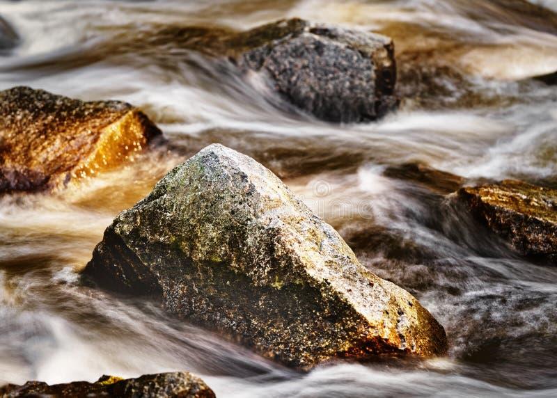 Große Steine in flüssigem Wasser am Abendlicht lizenzfreie stockfotografie
