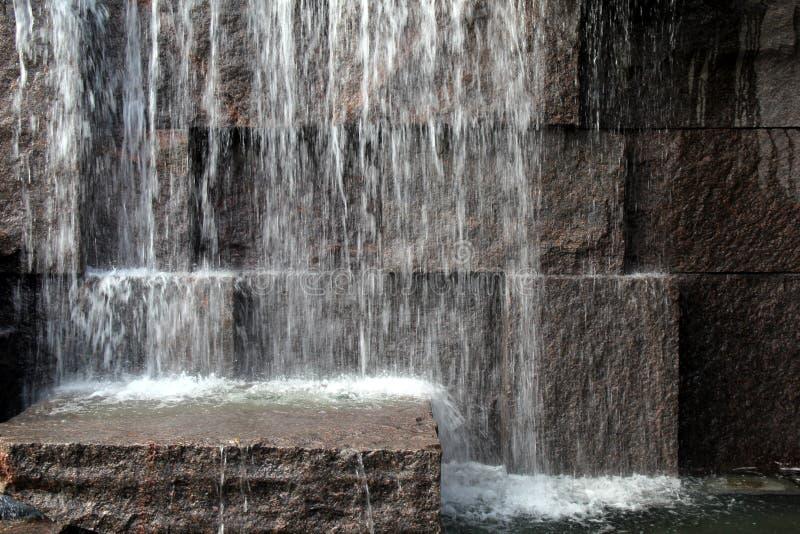 Große Steinwand mit Wasser, das von oben spritzt lizenzfreie stockfotos