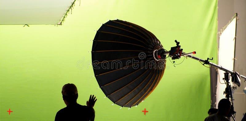 Große Studiolichtausrüstungen und Mann und grüner Schirm lizenzfreies stockbild