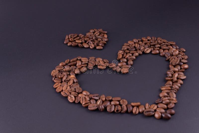 Große und kleine Herzen vom Kaffee in der unteren rechter Ecke auf einem dunklen Hintergrund lizenzfreie stockfotografie