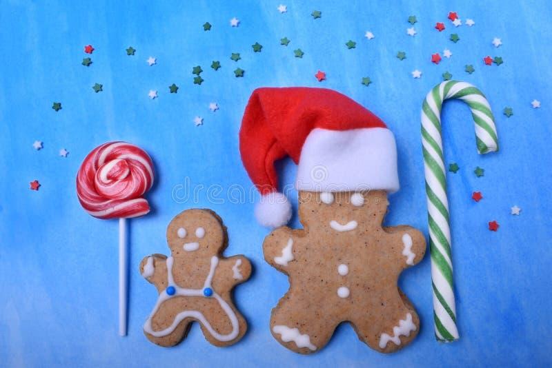 Große und kleine Lebkuchenmänner mit Lutschern und Santa Claus-Hut Süßigkeiten besprühen herum gegen den blauen Hintergrund lizenzfreie stockfotos