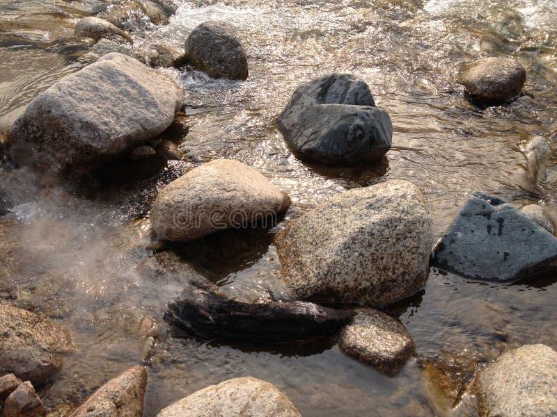 Große und kleine Steine von verschiedenen geometrischen Formen im Wasser lizenzfreie stockfotografie