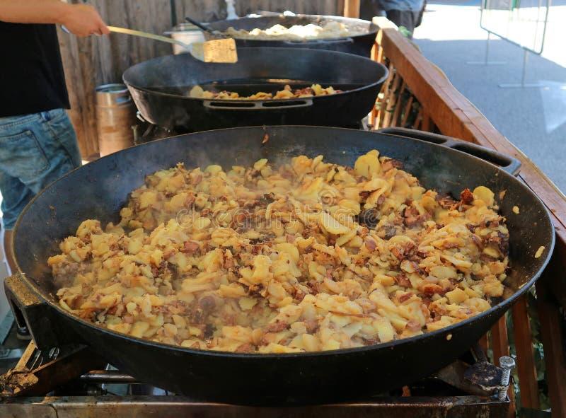 Große Wanne des Dämpfens von Grostl, von traditioneller österreichischer Mahlzeit gemacht von den Kartoffeln, von der Schweinswur stockbilder