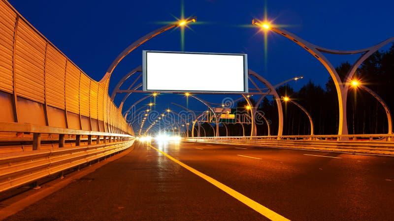 Große weiße Anschlagtafel auf Nachtlandstraße stockbild